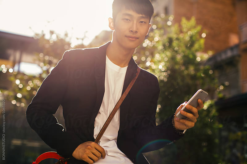 Portrait of a young asian businessman using his phone on the street.  by BONNINSTUDIO for Stocksy United