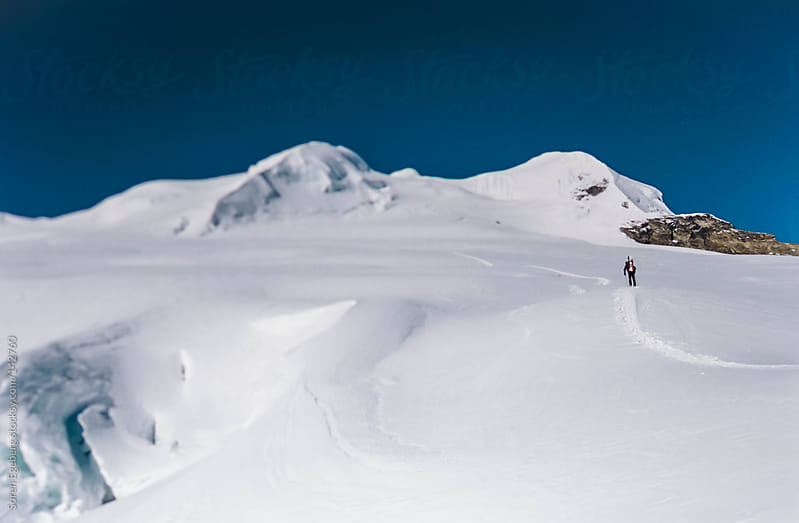 Snowboarder climbing up a snowy mountain peak in Nepal's Himalay by Soren Egeberg for Stocksy United