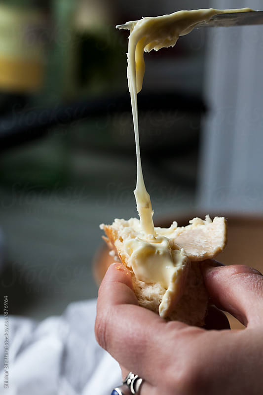 Spreading cheese on a slice of bread. by Shikhar Bhattarai for Stocksy United