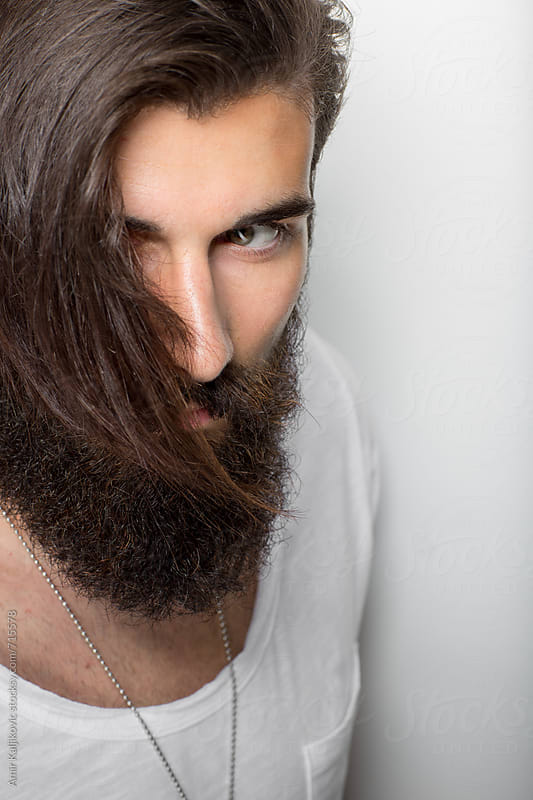 Closeup portrait of a male face with long brown beard by Amir Kaljikovic for Stocksy United