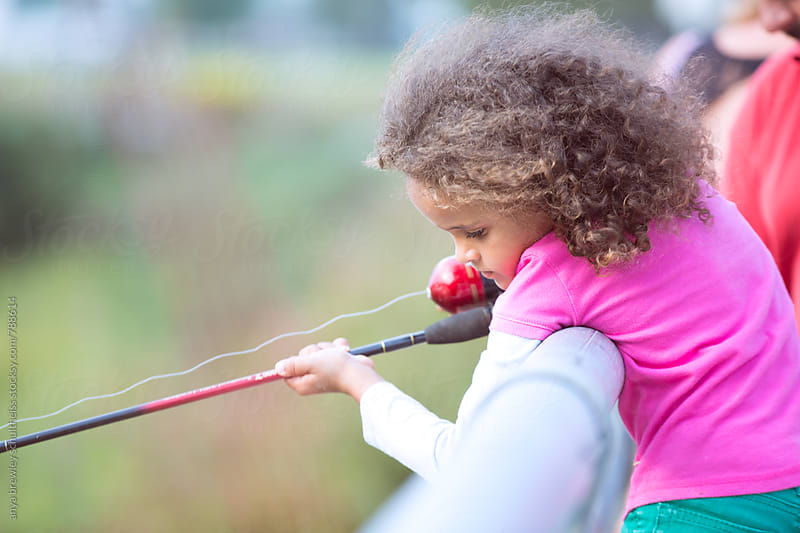 Portrait of young girl leaning slightly over the side of a bridge rail while holding a fishing rod. by anya brewley schultheiss for Stocksy United
