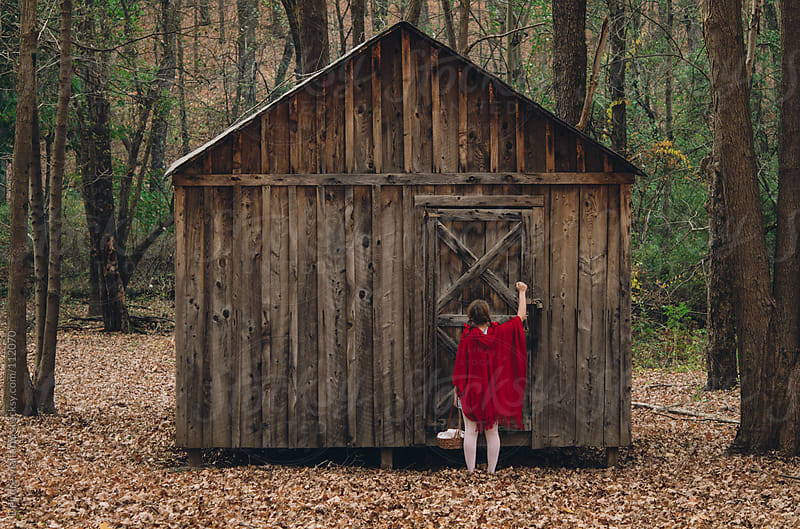girl in red knocks on door of cabin by Deirdre Malfatto for Stocksy United