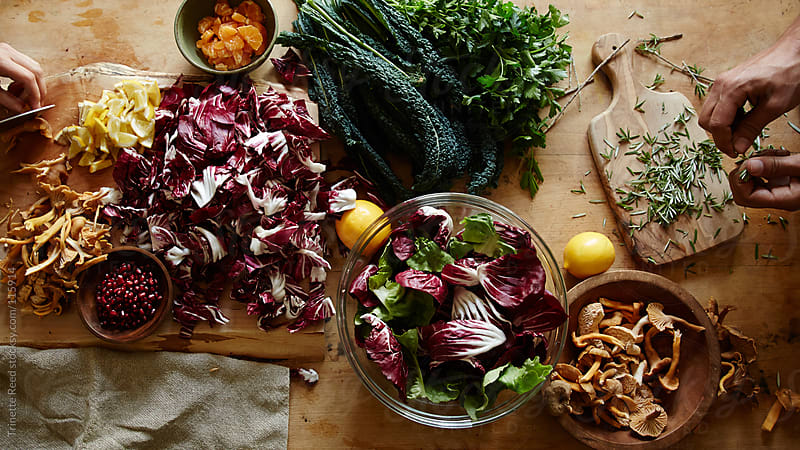 Couple cooking with lots of vegetable ingredients in the kitchen by Trinette Reed for Stocksy United