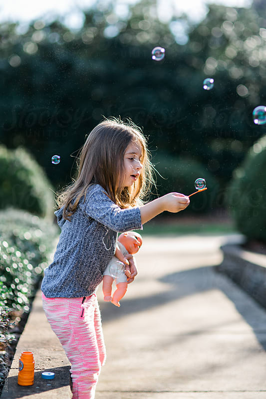 Cute young girl catching a bubble while holding her baby doll by Jakob for Stocksy United