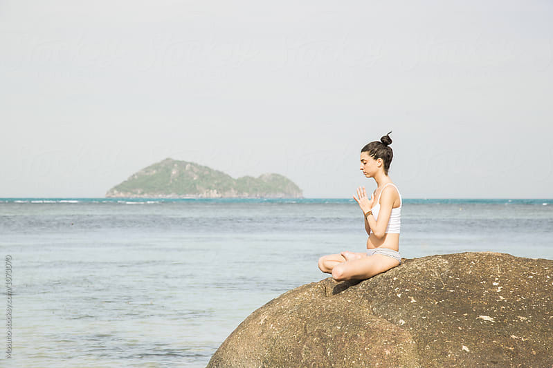 Woman Meditating on the Rock by Mosuno for Stocksy United