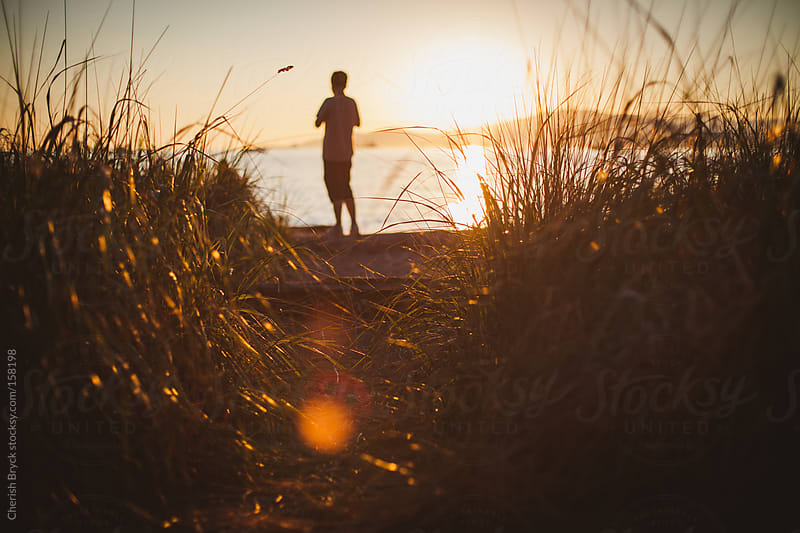 A boy at the shore during sunset. by Cherish Bryck for Stocksy United