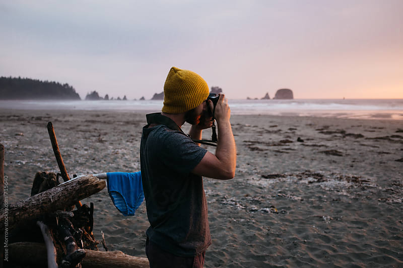 young male taking photos of sunset from camp by Jesse Morrow for Stocksy United