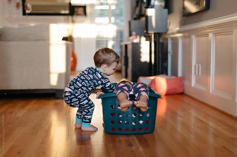 Two young children playing with a laundry basket by Jakob for Stocksy United