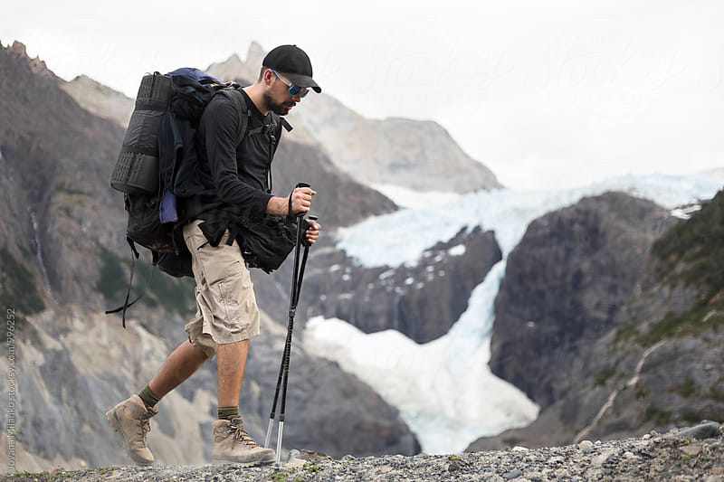 Man trekking with his heavy backpack next to a glacier in Torres Del Paine National Park in Chilean Patagonia by Jovana Milanko for Stocksy United