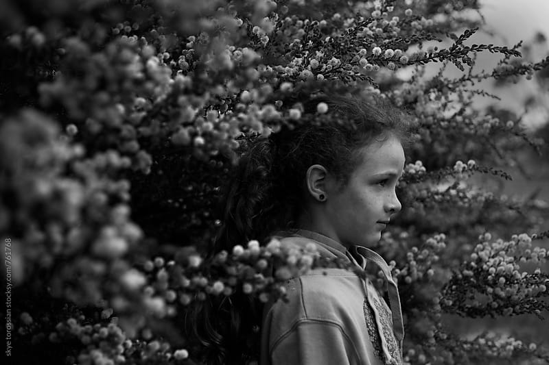 portrait of a young girl amongst blossoms by skye torossian for Stocksy United
