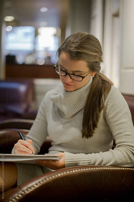 Young woman doing homework in student center by Brian McEntire for Stocksy United