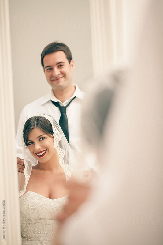 Bride and Groom Looking at Themselves in the Mirror by Lumina for Stocksy United