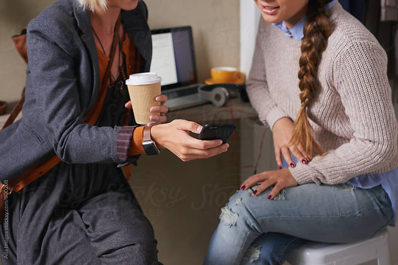Stylish young women discuss data on smartwatch connected to smartphone by Aila Images for Stocksy United