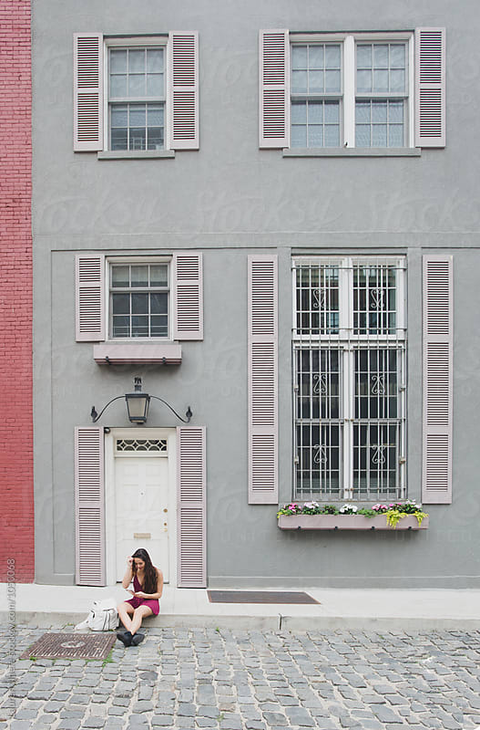 Young woman in front of quaint townhouse by Lauren Naefe for Stocksy United