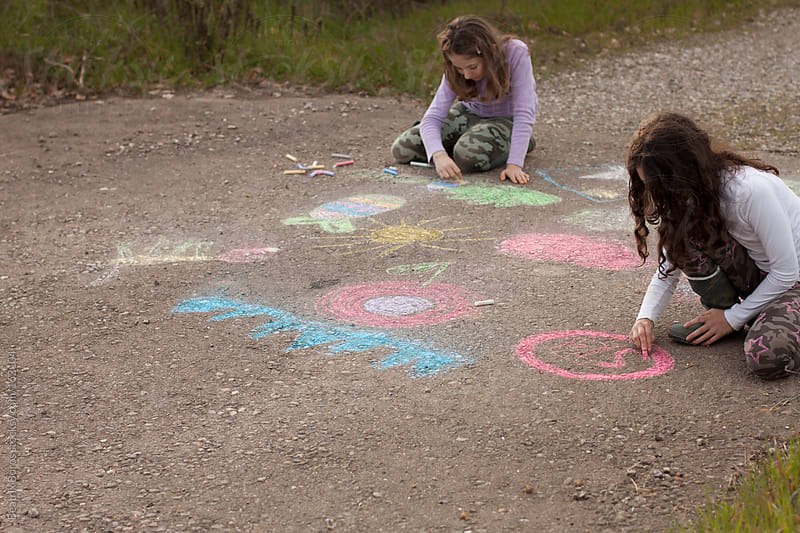 Two girls drawing with chalk on the road by Beatrix Boros for Stocksy United