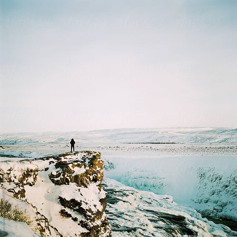 A figure stands at the edge of Gulfoss waterfall by Sam Burton for Stocksy United