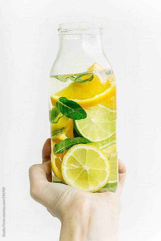 Bottle of fresh citrus drink in hand by Studio Firma for Stocksy United