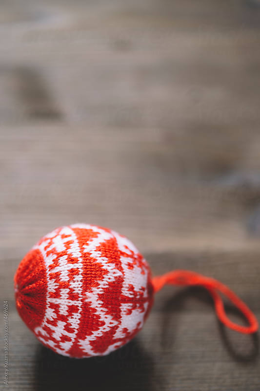 Red Christmas Ornament on Wooden Floor in closeup by Alexey Kuzma for Stocksy United