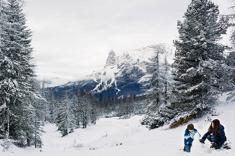 Snowman builder siblings with a scenic  Winter mountain view  by Beatrix Boros for Stocksy United