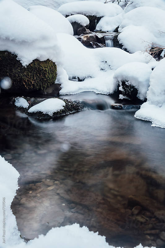 snow covered rocks and a little stream of water by Juri Pozzi for Stocksy United