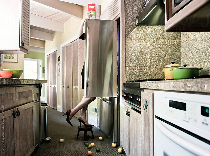 Woman looking into the refrigerator with heels on and holding a milk carton by Carolyn Lagattuta for Stocksy United