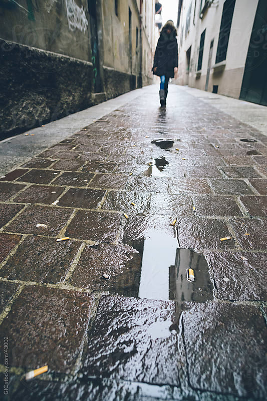 Woman walking in a street during a rainy day by GIC for Stocksy United