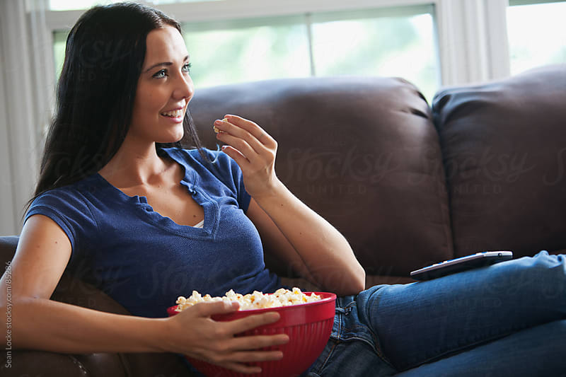 Television: Woman Watching TV With Bowl of Popcorn by Sean Locke for Stocksy United
