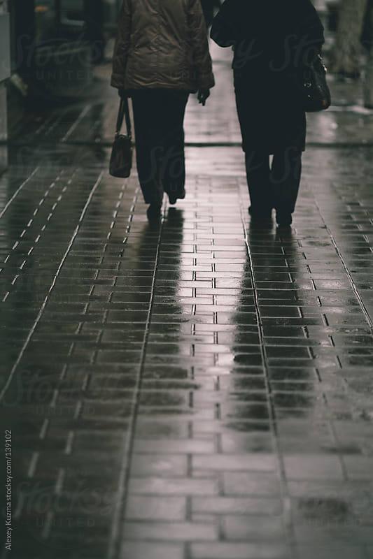 two women walking down the street by Alexey Kuzma for Stocksy United