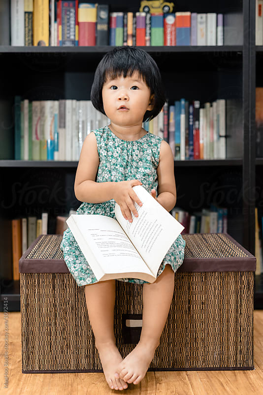 Adorable toddler girl reading book at home by MaaHoo Studio for Stocksy United