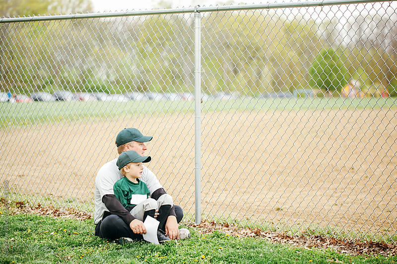 father and son watching a baseball game by Kelly Knox for Stocksy United