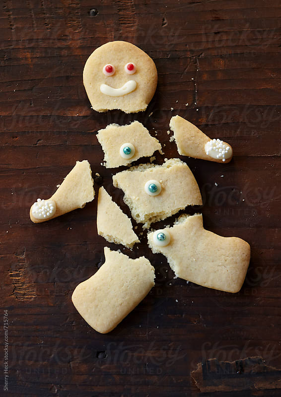 Broken sugar cookie man on dark wood surface by Sherry Heck for Stocksy United