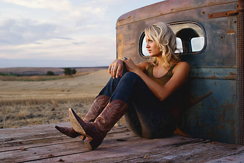 Young woman sitting on back of old flatbed truck.  by Tana Teel for Stocksy United