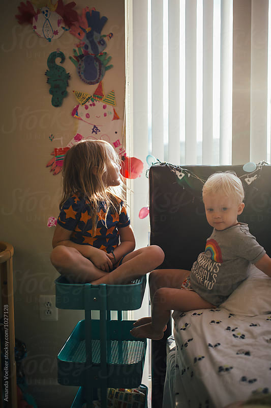 A little brother and sister sit together in their room by Amanda Voelker for Stocksy United