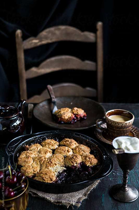 Cherry cobbler with a chair in the background by Aniko Lueff Takacs for Stocksy United