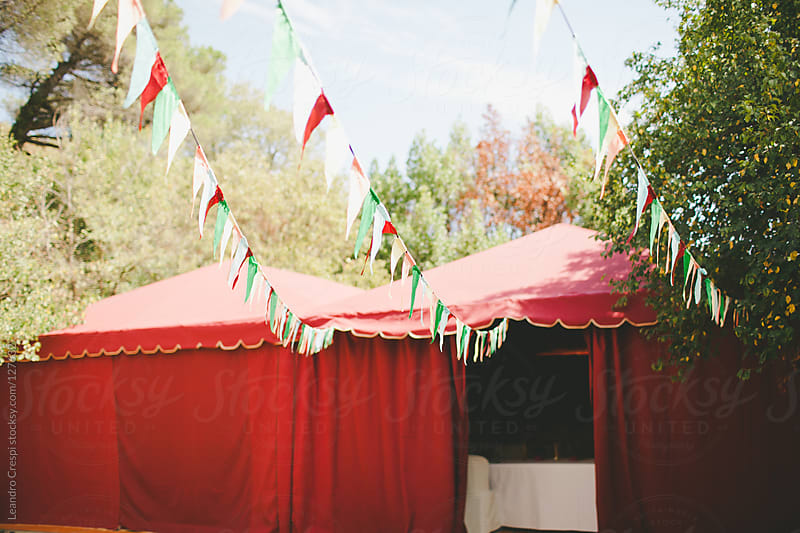 Party tent and flags on wedding day by Leandro Crespi for Stocksy United