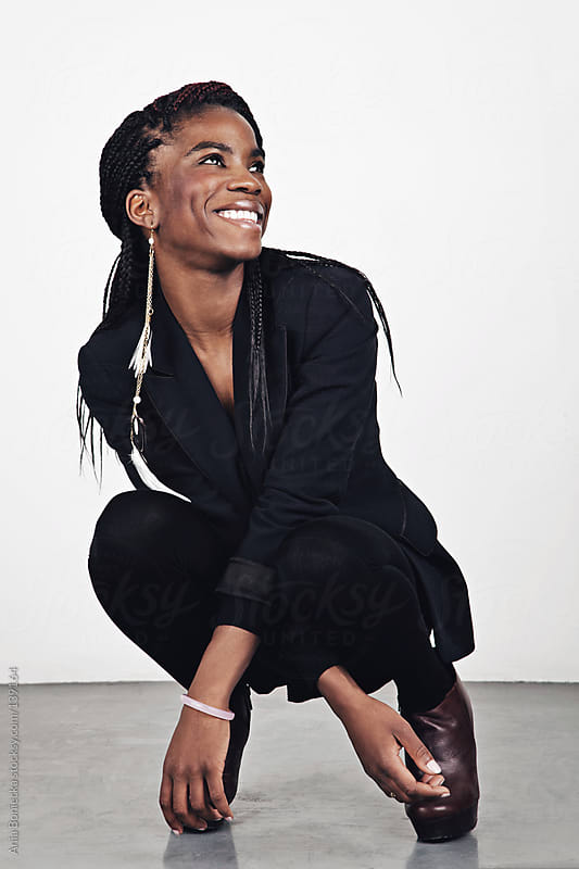 A black woman in a suit smiling by Ania Boniecka for Stocksy United