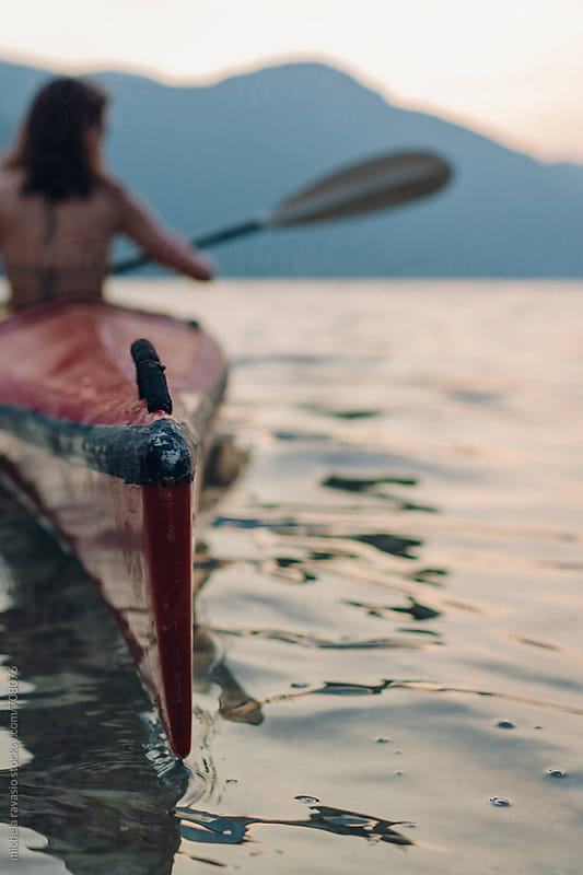 Woman enjoying the canoeing at sunset by michela ravasio for Stocksy United