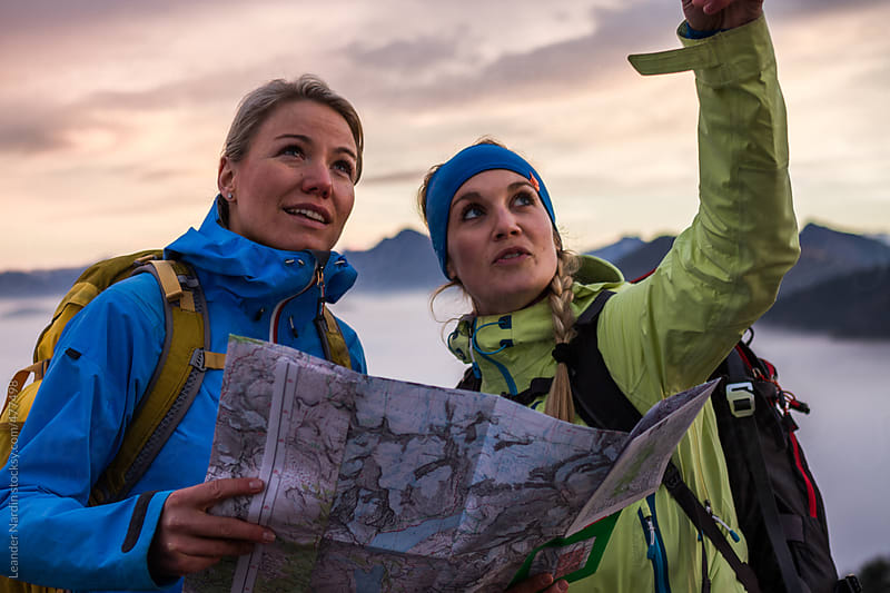 two female hiker reading a hiking map planing a route by Leander Nardin for Stocksy United