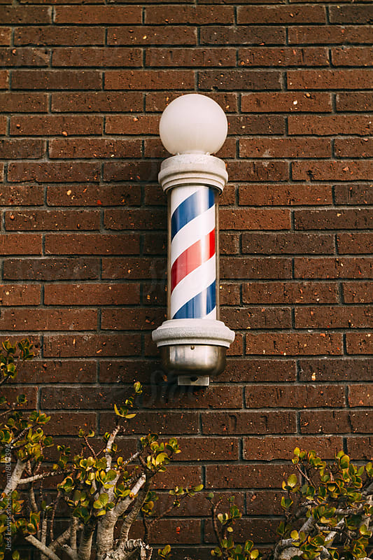 barber pole on a brick wall by Jess Lewis for Stocksy United