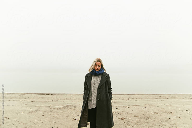 Beautiful woman standing on the beach during the fog - horizontal by Marija Kovac for Stocksy United