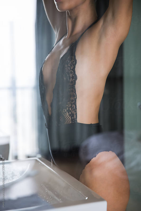 Morning routine - woman in sexy lingerie in front of a mirror  by Jovo Jovanovic for Stocksy United