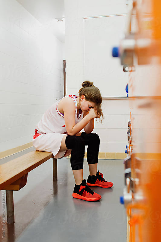 female basketball player sits on bench in locker room by Tana Teel for Stocksy United