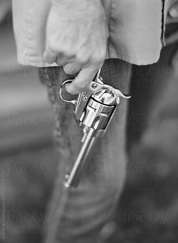 older woman holding a gun by Kirill Bordon photography for Stocksy United