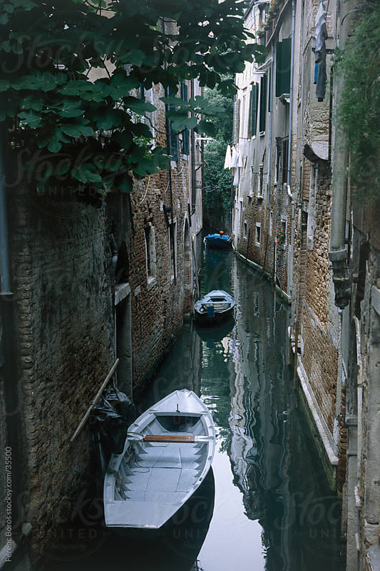 Narrow canal with flat-boats in Venice by Ferenc Boros for Stocksy United