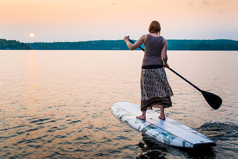 Woman Wearing Dress On Stand Up Paddle Board At Cottage Lake by JP Danko for Stocksy United