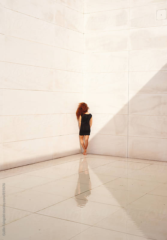 Young woman standing in corner. Concept by Guille Faingold for Stocksy United