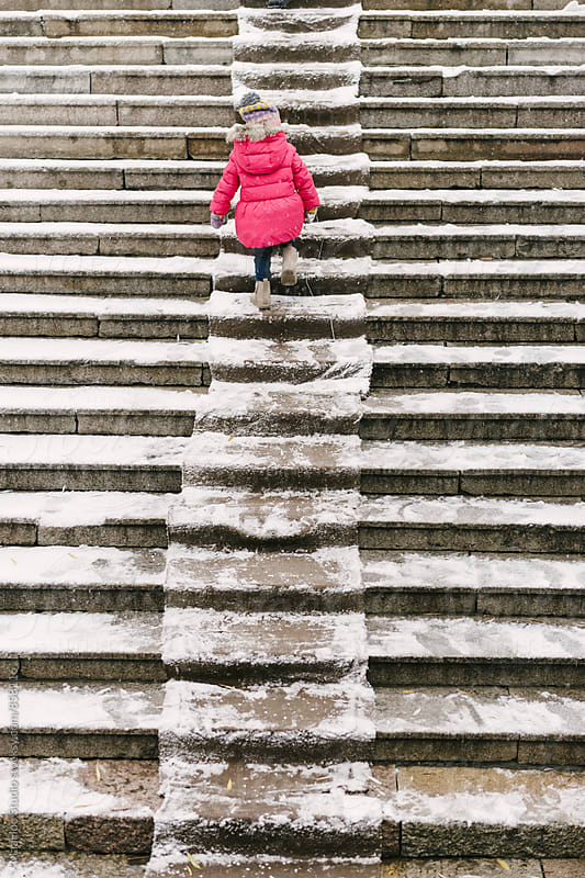 Baby girl climbing stairs in snow by Maa Hoo for Stocksy United