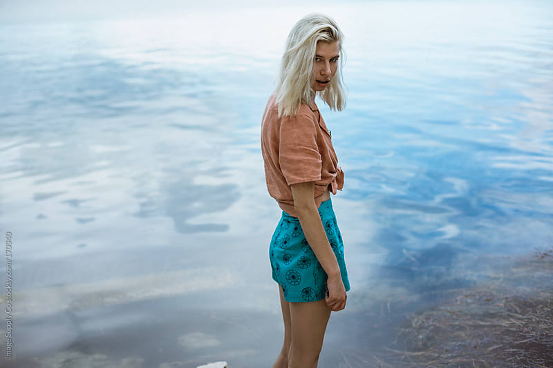 Blond girl standing lakeside by Image Supply Co for Stocksy United