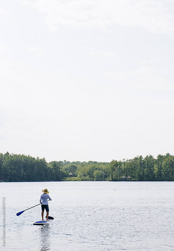 Woman paddleboarding on a lake in summer by Cara Dolan for Stocksy United