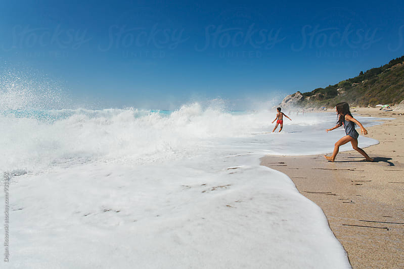 Children playing with wave by Dejan Ristovski for Stocksy United